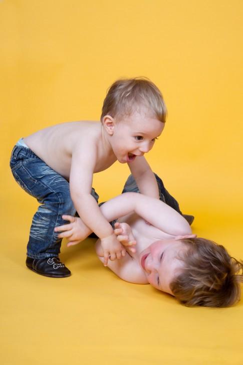 Geschwisterportrait. Die Kleinkinder spielen miteinander. Ein Kind liegt auf gelbem Hintergrund auf dem Boden. Das andere ist über ihn gebeugt. Beide Kinder haben den Oberkörper frei und eine Jeans an.