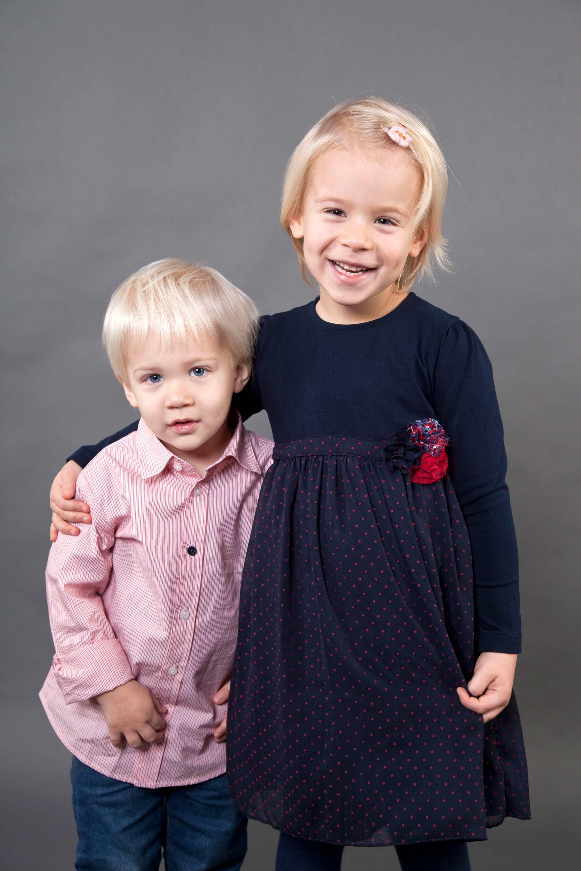 Geschwisterportrait Bruder und Schwester. Das ältere blonde Mädchen hält ihren Arm um den kleineren blonden Bruder. Das Mädchen trägt ein blaues Kleid mit roten Punkten. Der Junge trägt ein rotweiß gestreiftes Hemd und Jeans.