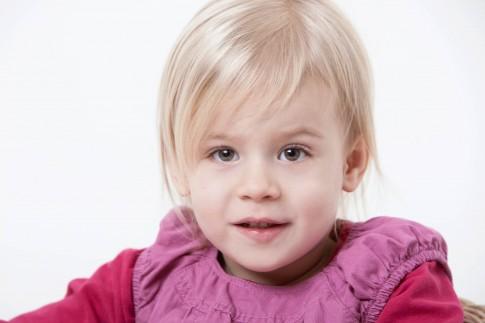 Einzelportrait eines Mädchens. Das blonde Mädchen trägt ein lilarotes Oberteil und sieht mit leicht geöffnetem Mund in die Kamera.