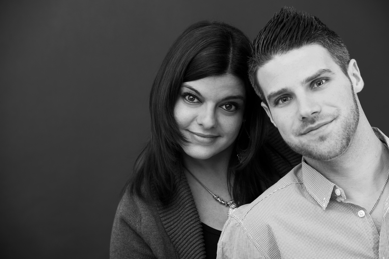 Paarshooting in schwarz und weiß. Die Frau steht hinter dem Mann. Beide neigen ihren Kopf zum anderen. Beide sehen lächelnd in die Kamera.