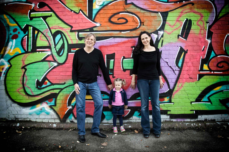 Familienshooting vor einer Graffiti Wand. Vater und Mutter haben ein schwarzes Oberteil und eine blaue Jeans an. Die Eltern stehen außen und die Tochter mittig.