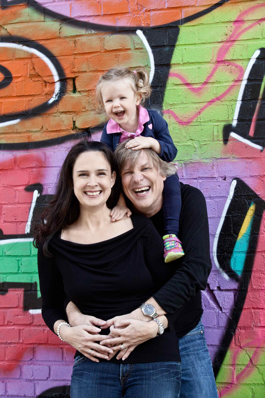 Familienshooting vor einer Graffiti Wand. Der Vater trägt seine Tochter auf den Schultern. Er umarmt seine Frau, die vor ihm steht, und ihre Hände liegen auf ihrem Bauch aufeinander. Alle lachen in die Kamera.