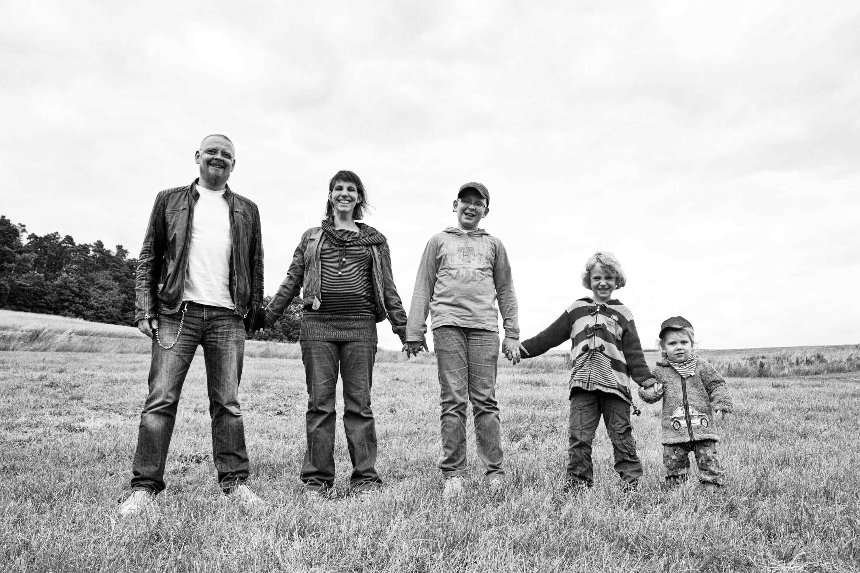 Die Familie steht aneinander gereiht auf einer Wiese. Sie halten sich an den Händen. Von links nach rechts der Größe nach Vater, Mutter und drei Kinder.