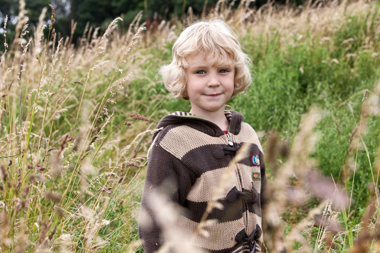Einzelportrait eines Kindes. Das Kind steht in einer hohen verwilderten Wiese. Es hat eine braun gestreifte Jacke an. Es sieht mit einem Lächeln in die Kamera.