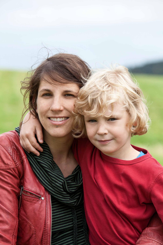 Mutter und Sohn Foto. Die Mutter hat ihren Sohn im Arm. Der Sohn legt seinen Arm um den Hals der Mutter. Beide haben was rotes an.
