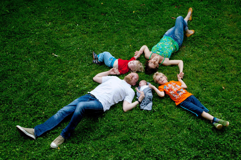 Familienfoto auf einer Wiese. Die Familie liegt in Sternform auf dem Rücken. Sie halten sich an den Händen und schauen nach oben in die Kamera. Vater und Mutter liegen sich gegenüber.