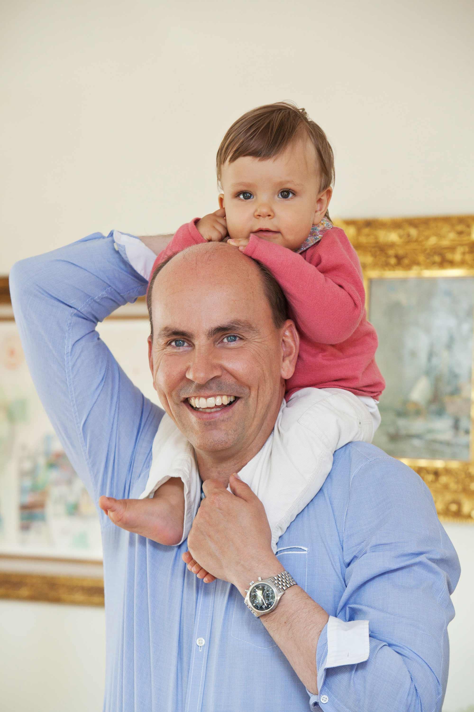 Der Vater hat sein Kind auf den Schultern. Er hält es am Rücken mit der einen Hand und am Füßchen mit der anderen Hand. Im Hintergrund sind zwei Bilder abgebildet. Der Mann lacht in die Kamera.