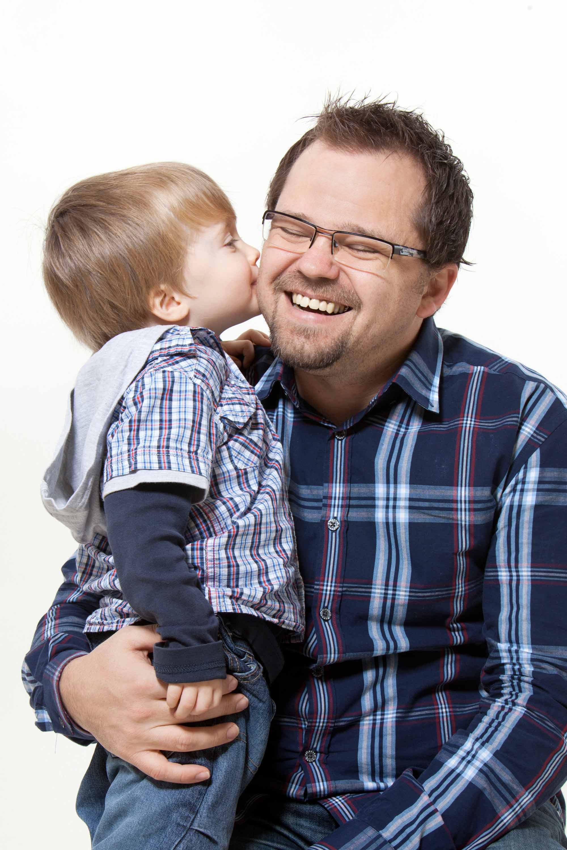 Das Kind hat seinen Mund ganz nah an der Wange bzw. am Ohr des Vaters. Der Vater lacht. Er hält das Kind in seinem Arm und drückt es an sich. Beide haben karierte Oberteile an.