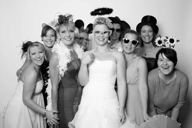 Die Braut steht in der Mitte zahlreicher Frauen. Alle lachen in die Kamera und haben ein Verkleidungsaccessoire auf. Das Bild ist in schwarz und weiß gehalten.