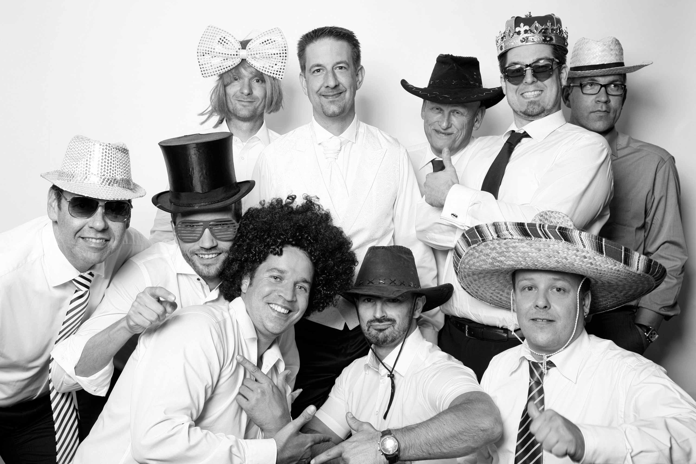 Der Bräutigam steht in der Mitte zahlreicher Männer. Alle lachen in die Kamera und haben ein Verkleidungsaccessoire auf. Ob Hut, Brille, Krone oder Maske. Das Bild ist in schwarz und weiß gehalten.