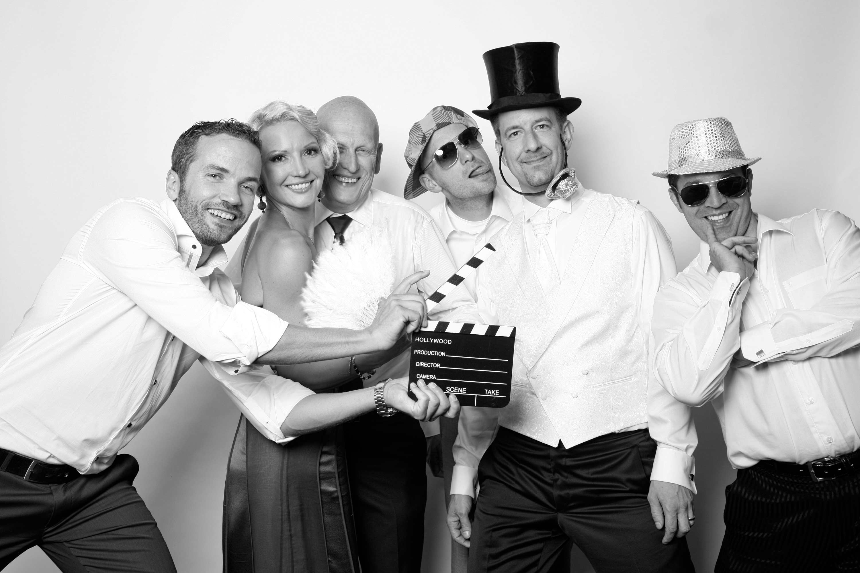 Sechs Personen sind auf dem Bild in der Fotobox zu sehen. Die Männer tragen alle weiße Hemden. Die Frau ein Kleid. Einer der Gäste hält vor die anderen eine Filmklappe.