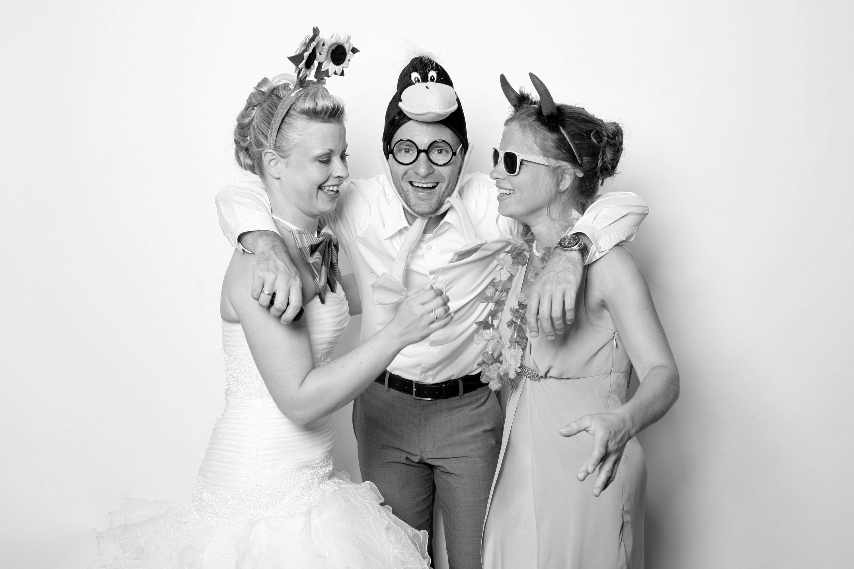 Die Braut steht mit einem Mann und einer Frau in der Fotobox. Der Mann hält die Frauen zur rechten und zur linken umarmt. Die Frauen sind zueinander gerichtet. Der Mann trägt eine Entenkopfbekleidung. Er sieht in die Kamera.