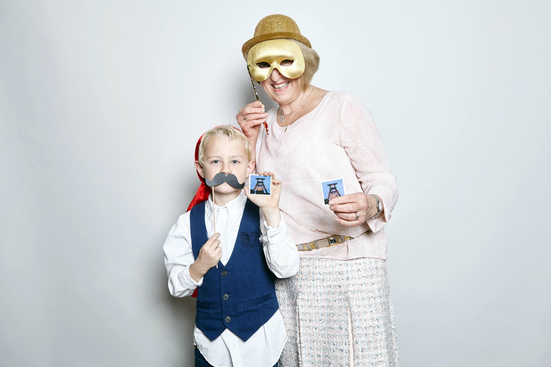 Ein Junge und eine Frau, die beide das gleiche Memoryteil in der Hand halten, stehen in der Fotobox. Der Junge hält sich einen Papierschnurrbart vor den Mund und die Frau eine goldenen Maske vor die Augen.