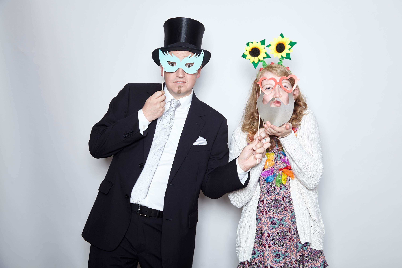 Ein Mann im schwarzen Anzug und eine Frau im buntem Kleid und weißer Strickjacke sind abgebildet. Der Mann trägt einen Zylinder und hält sich eine blaue Maske vor die Augen. Die Frau hat einen Sonnenblumenhaarreifen auf und hält sich einen Papierbart vors Kinn.