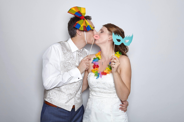 Das Brautpaar küsst sich in der Fotobox. Der Bräutigam hält seinen Kussmund aus Papier vor die Lippen des Brautpaares. Beide haben die Augen geschlossen.