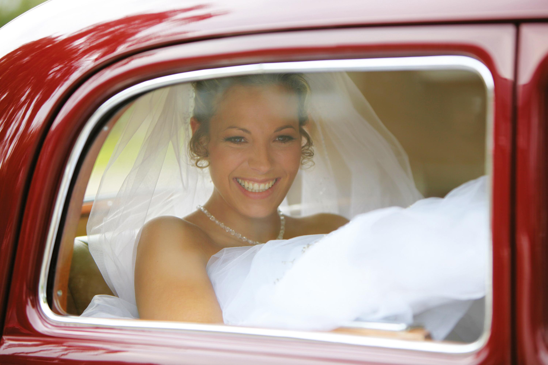 Die Braut, in einem weißen Hochzeitskleid, sitzt in einem roten Auto, Sie lacht in die Kamera.