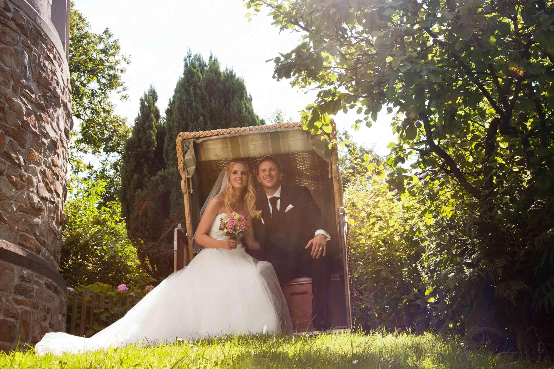 Das Hochzeitspaar sitz in einem Strandkorb in einem grünen Garten. Die Sonne scheint hell und beide lachen. Die Braut hält einen Brautstrauß in der Hand. Sie trägt ein langes, weißes Brautkleid.