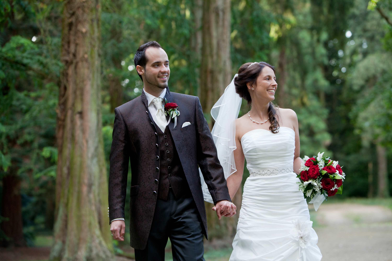 Das Brautpaar geht Hand in Hand einen Waldweg entlang. Beide schauen in die gleiche Richtung. Die braut trägt ein weißes Brautkleid.
