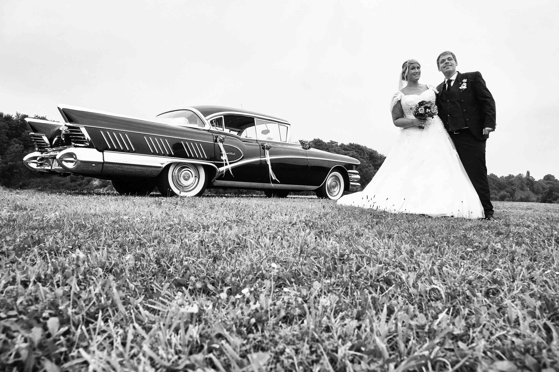 Das Brautpaar steht gemeinsam vor einem Oldtimer auf einer Wiese. Schwarz-weiß-Foto.