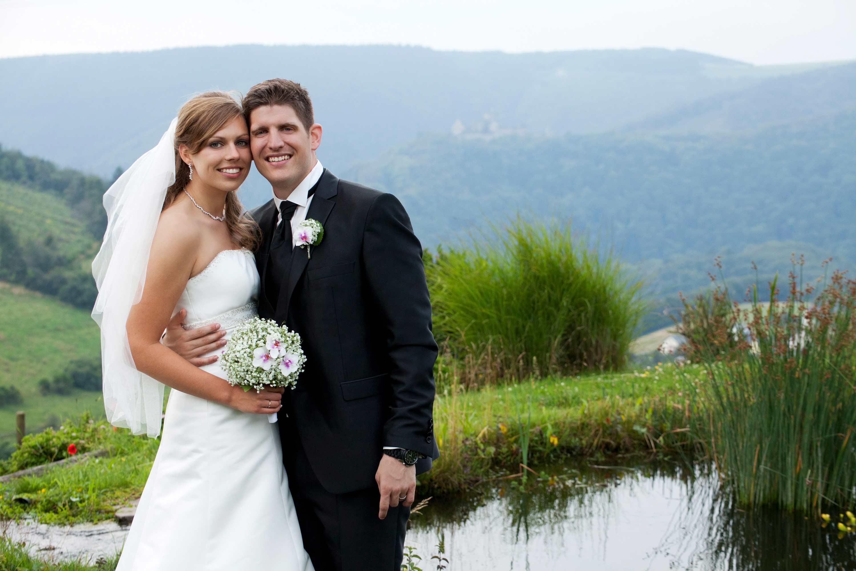 Das Brautpaar steht Arm in Arm vor einem kleinen Teich. Umgeben von einer weiten Landschaft.