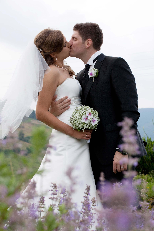 Das Brautpaar küsst sich. Der Bräutigam hält seine Braut im Arm. Ihr Schleier weht im Wind. Die Braut hält einen Brautstrauß in der Hand. Im Vordergrund sind rosa Blumen.