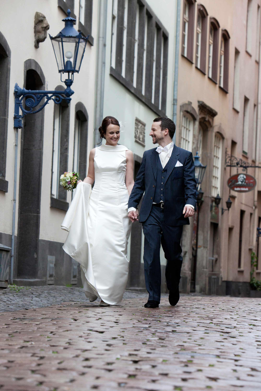 Das Brautpaar geht Hand in Hand auf Kopfsteinpflaster durch eine Gasse in Köln. Im Hintergrund sind Häuser zu sehen und eine historische, blaue Laterne. Der Bräutigam schaut die Braut lachend an. Die Braut trägt ein weißes Brautkleid und hält einen Brautstrauß in der Hand.