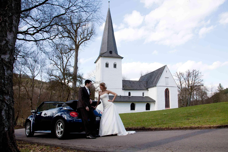 Das Brautpaar lehnt sich lässig an das dunkelblaue Hochzeitsauto. Im Hintergrund ist eine kleine, weiße Kirche. Es ist Winter und die Bäume sind kahl.