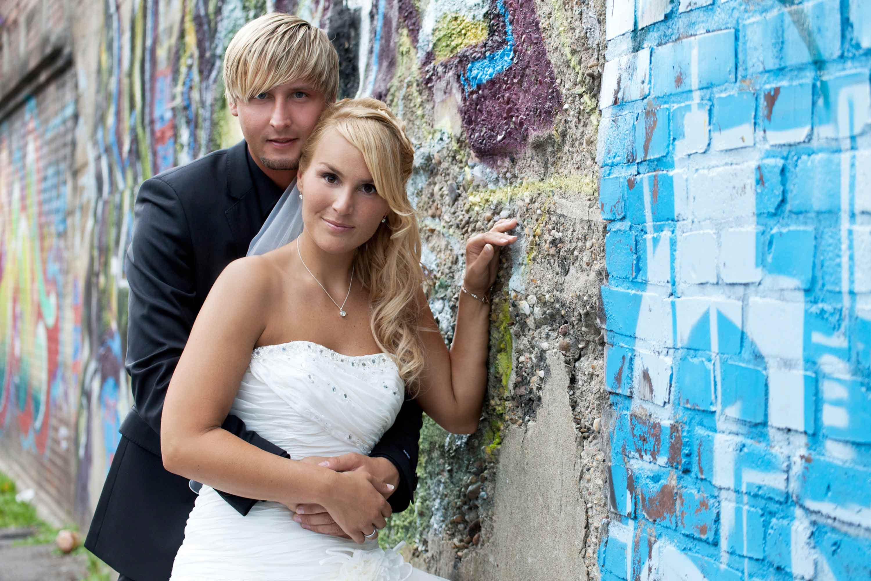 Das Brautpaar steht zusammen angelehnt an eine Grafittiwand. Der Bräutigam hält die Braut im Arm.