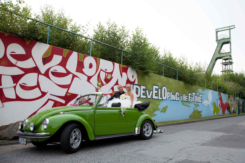 Das Brautpaar sitzt in einem grünen VW Käfer Cabrio. Im Hintergrund ist eine Grafittwand und ein alter Förderturm.