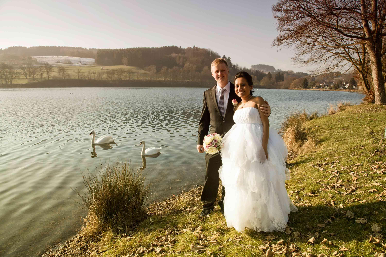 Das Brautpaar steht im Sonnenlicht an einem See. Auf dem See sind zwei weiße Schwäne. Der Bräutigam hält die Braut im Arm. Die Braut hält einen Brautstrauß in der Hand. Beide lachen.