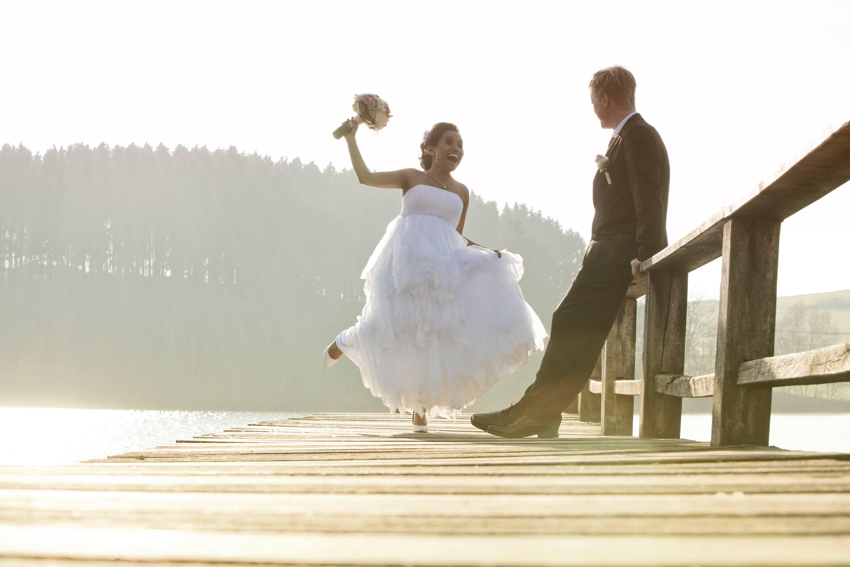 Das Brautpaar steht auf einem Holzsteg im gleißenden Sonnenlicht an einem See. Der Bräutigam lehnt sich lässig an das hölzerne Geländer. Die Braut hebt den Arm mit dem Brautstrauß in die Luft.
