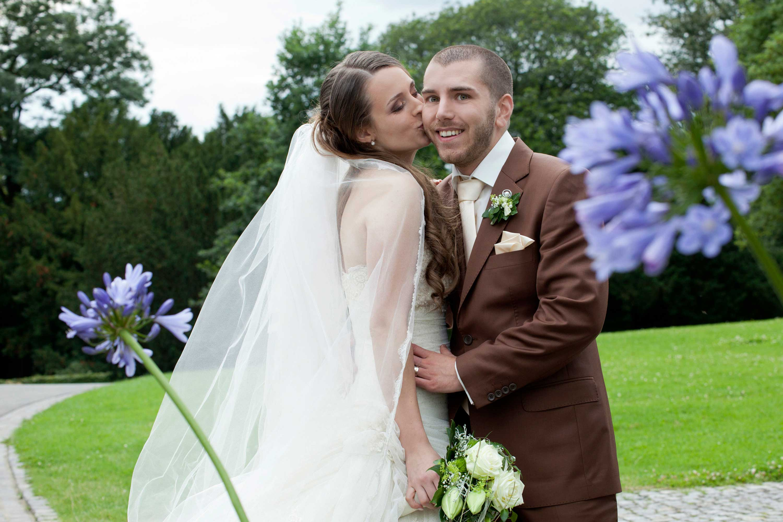 Das Brautpaar steht zueinander gewandt in einem grünen Park. Im Vordergrund sind zwei violette Blumen. Die Braut küsst den Bräutigam mit geschlossenen Augen. Der Bräutigam trägt einen brauen Anzug. Die Braut hält einen Brautstrauß in der Hand.
