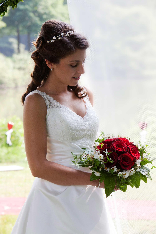 Die Braut blickt auf ihren Brautstrauß mit roten Rosen.