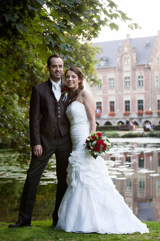Das Brautpaar steht Arm in Arm vor einem See mit Seerosen. Im Hintergrund ist ein Schloss. Sie sind umgeben von grünen Blättern. Die Braut hält einen Brautstrauß in der Hand.