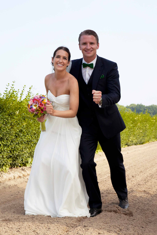 Das Brautpaar steht in Startposition auf einer sandigen Pferderennbahn. Die Braut hält einen Brautstrauß in der Hand. Beide lachen.