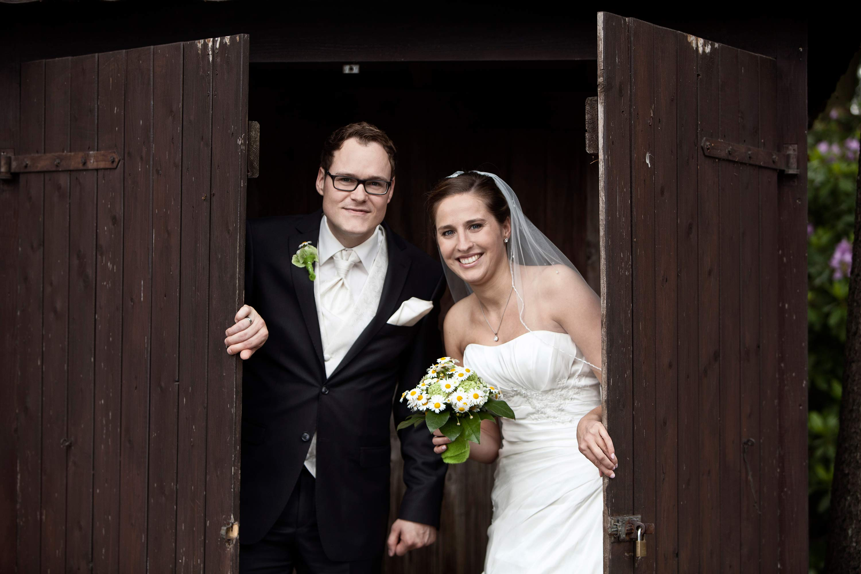 Das Brautpaar öffnet gemeinsam eine braune Holztür. Die Braut hält einen Brautstrauß in der Hand.