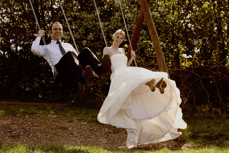 Das Brautpaar schaukelt gemeinsam. Beide lachen.