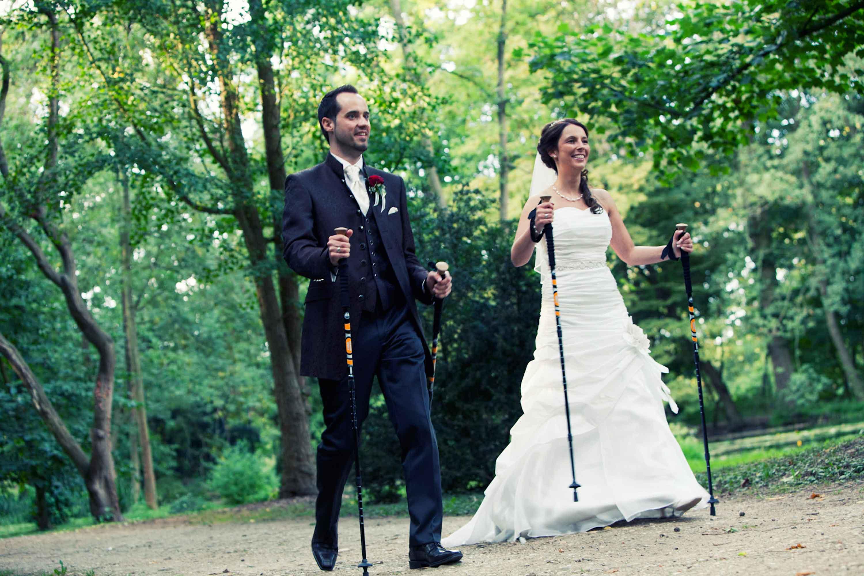 Das Brautpaar läuft mit Nordic Walking Stöcken nebeneinander einen Waldweg entlang. Beide lachen.