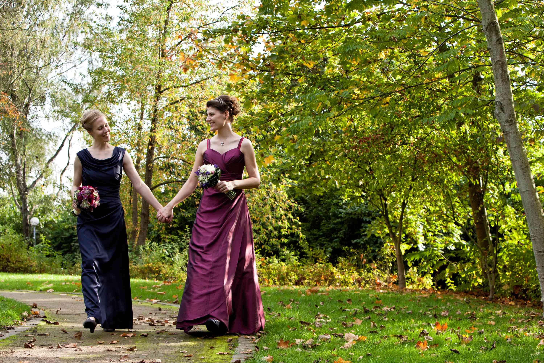 Das Brautpaar läuft Hand in Hand einen Waldweg entlang und schaut sich lächelnd an.