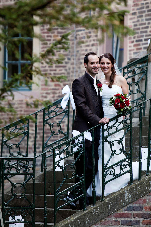 Das Brautpaar steht Arm in Arm nebeneinander auf einer Treppe. Der Bräutigam hält sich an dem dunkelgrünen Geländer fest. Die Braut hält einen Brautstrauß mit roten Rosen in der Hand. Sie sind umgeben von grünen Zweigen. Im Hintergrund ist ein Gebäude aus Backstein.