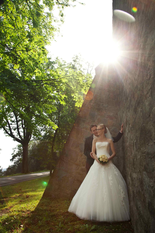 Das Brautpaar steht neben einer hohen Steinmauer. Das Gegenlicht strahlt. Im Hintergrund sind grüne Bäume.