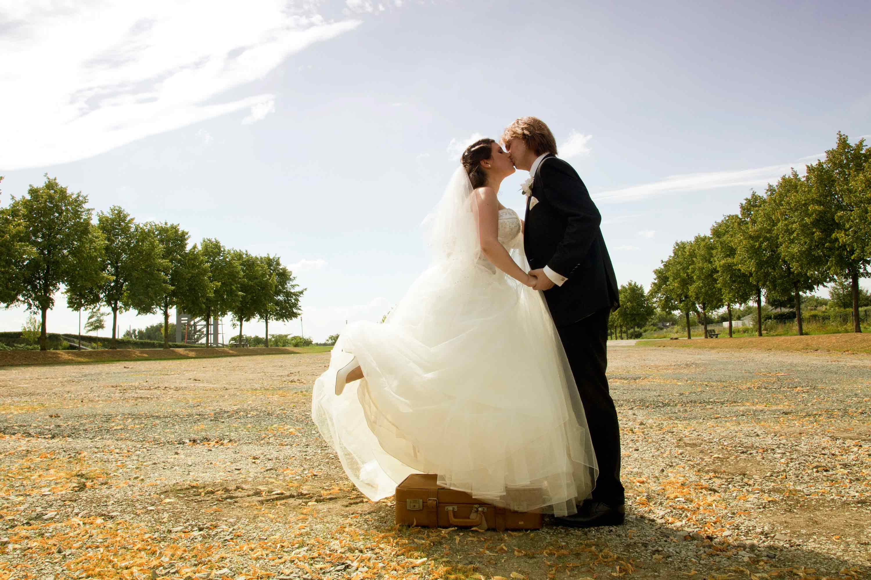 Das Brautpaar küsst sich auf einem breiten Weg mit Bäumen. Die Braut steht auf einem Koffer. Sie halten sich an den Händen.