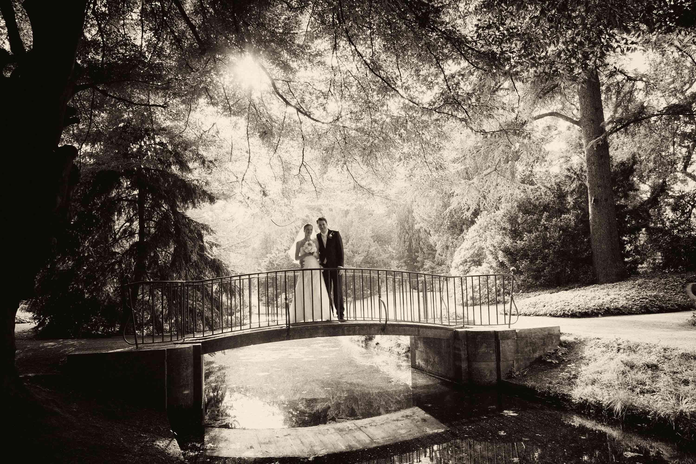 Das Brautpaar steht auf einer kleinen Brücke in einem Park. Die Sonne strahlt durch die Bäume. Schwarz-weiß-Foto.
