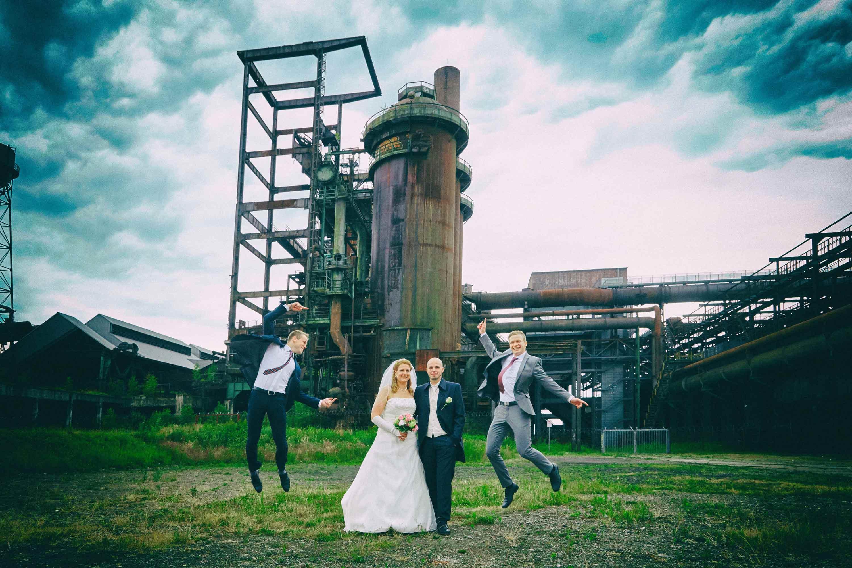 Das Brautpaar und die Trauzeugen sind auf einem brachliegendem Industriegelände. Das Brautpaar steht nebeneinander. Die Trauzeugen springen in die Luft.