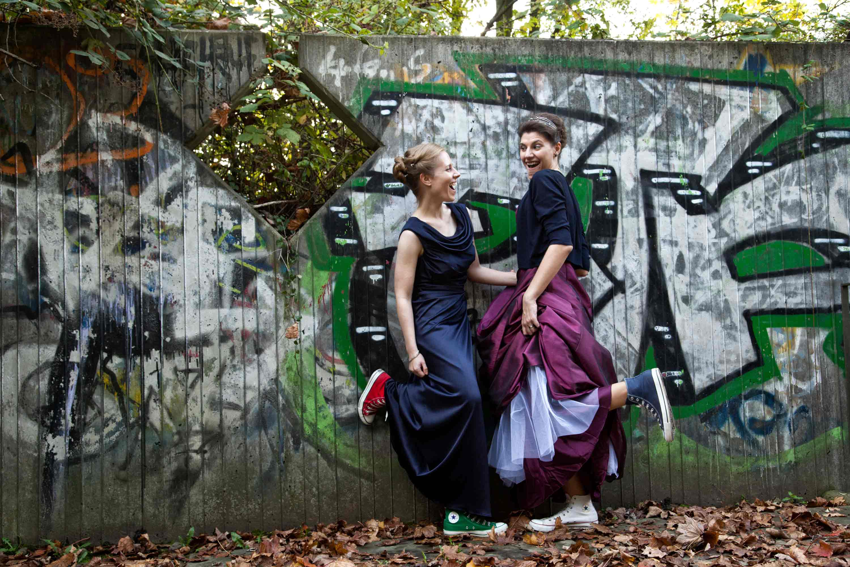 Das Brautpaar steht zueinander gewandt vor einer Grafittiwand. Beide lachen sich zu und tragen Chucks und heben jeweils einen Fuß. Auf dem Boden liegt braunes Laub.