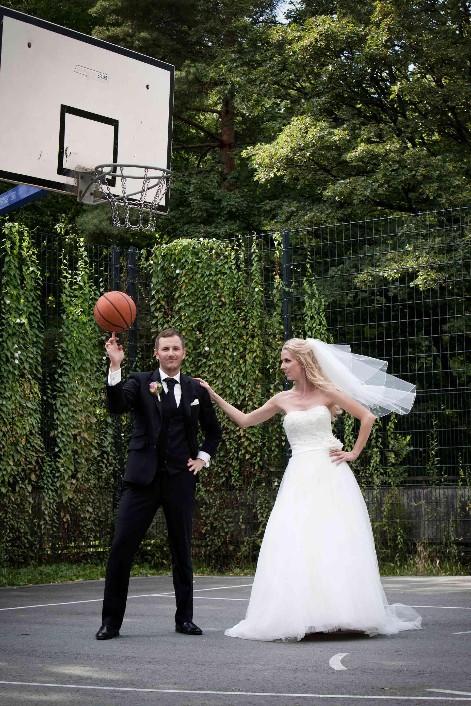 Das Brautpaar steht nebeneinander auf einem Basketballplatz. Der Bräutigam hält einen Basketball auf einem Finger in die Höhe. Die Braut legt ihre Hand auf seine Schulter und schaut ihn an. Ihr Schleier weht. Über den beiden ist der Basektballkorb.