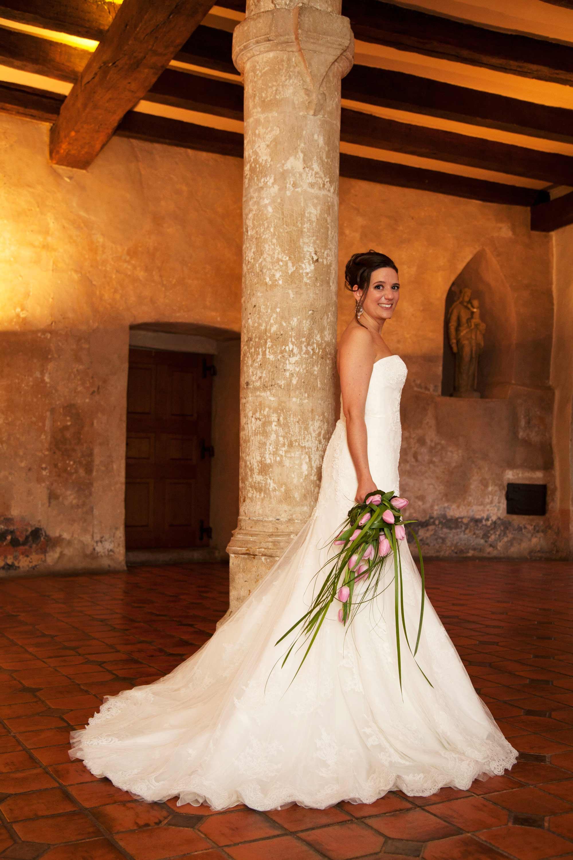 Die Braut steht in einem alten Saal an einer Steinsäule.Das Licht ist golden. An der Decke sind Holzbalken. Die Braut hält einen Brautstrauß in der Hand.