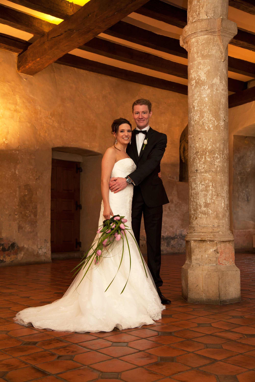 Das Brautpaar steht nebeneinander in einem alten Saal an einer Steinsäule.Das Licht ist golden. An der Decke sind Holzbalken. Die Braut hält einen Brautstrauß in der Hand. Der Bräutigam hält die Braut im Arm.