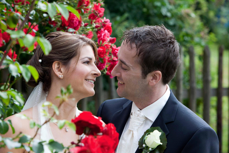 Das Brautpaar schaut sich lachend an und ist in einem grünen Garten umgeben von roten Rosen.