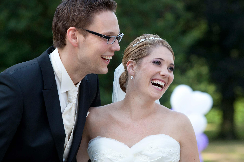 Das Brautpaar steht nebeneinander und schaut lachend in die gleiche Richtung.
